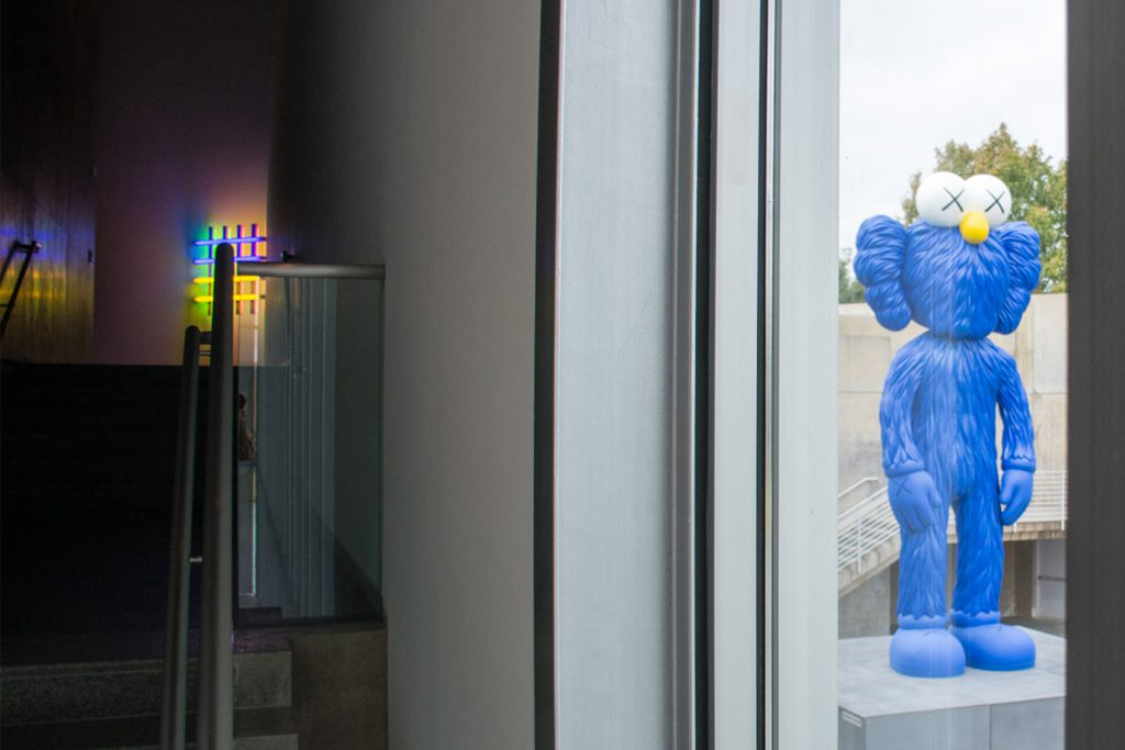 large KAWS sculpture through window of Ft. Worth Modern with Dan Flavin upstairs.