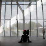 Silhouette of Kaws sculpture at Fort Worth Modern in front of reflecting pond