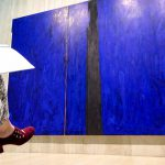 Big Blue painting by Clyfford Still as seen from behind woman with red shoes writing in a blank book